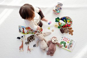 Baby surrounded by toys on white blanket