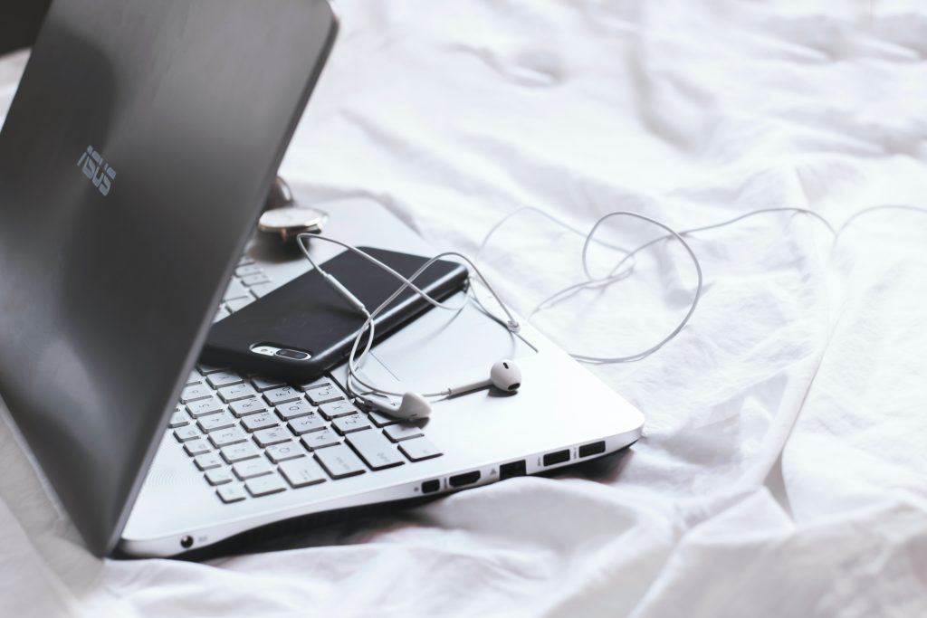 Laptop and smartphone on bed
