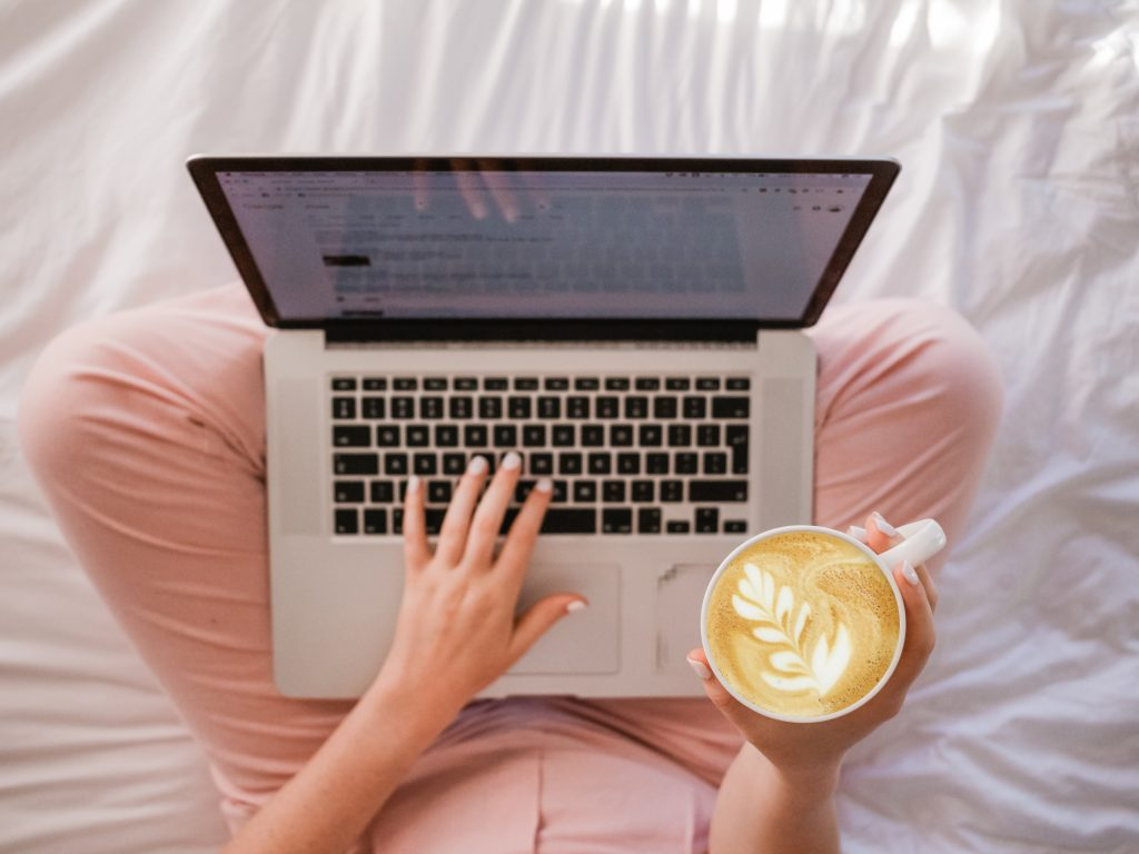 Laptop on lap of person wearing pink jeans with cup of coffee for online decluttering session