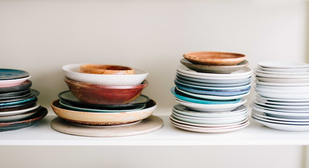 piles of plates in kitchen to declutter